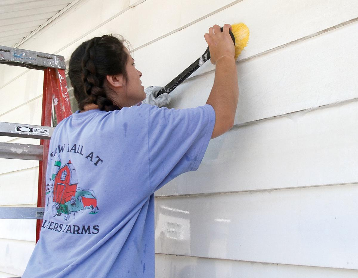 Anna Reed scrubs the siding of a house to be painted