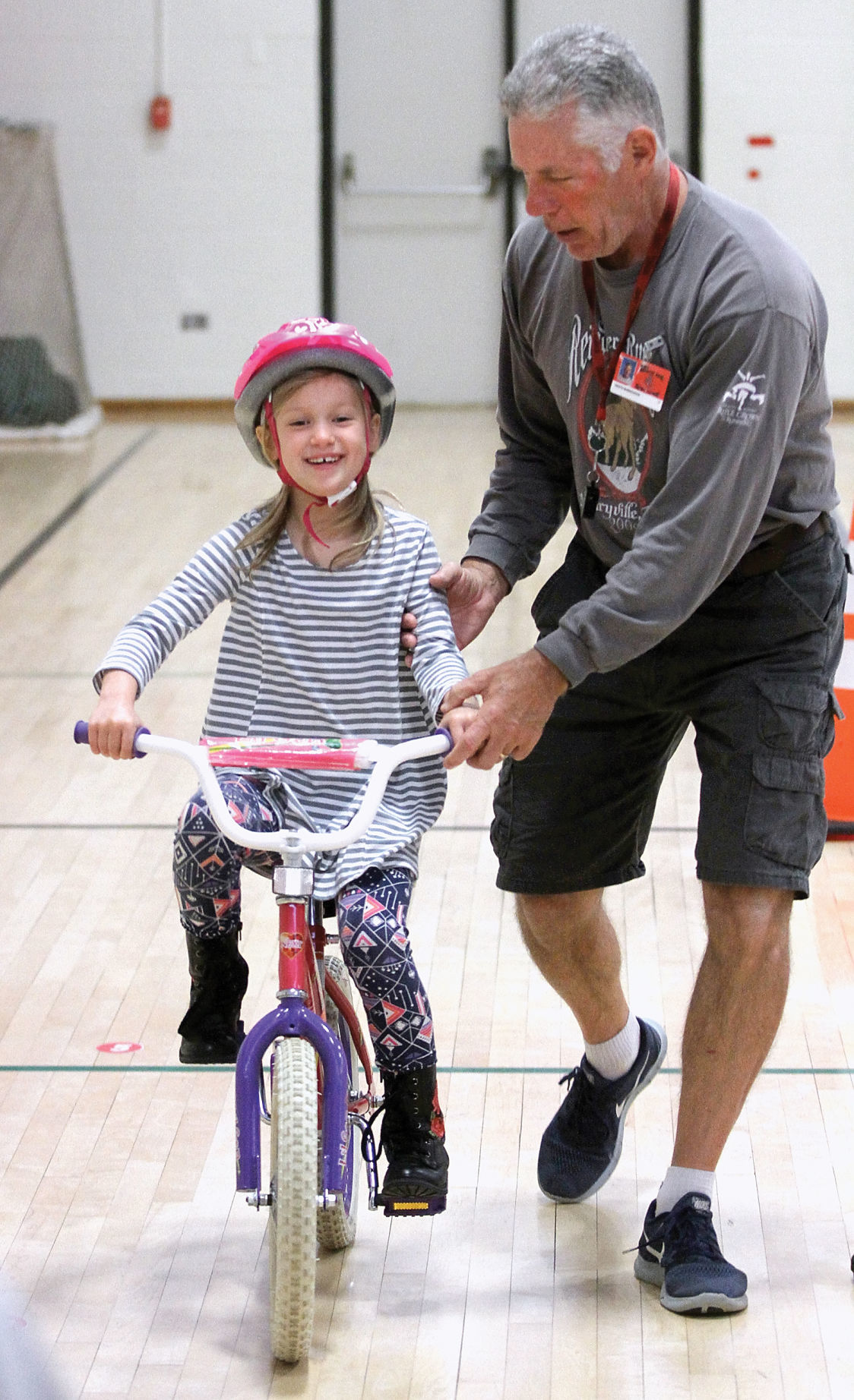 Keith Burroughs helps a John Sevier Elementary student learn to ride a bicycle