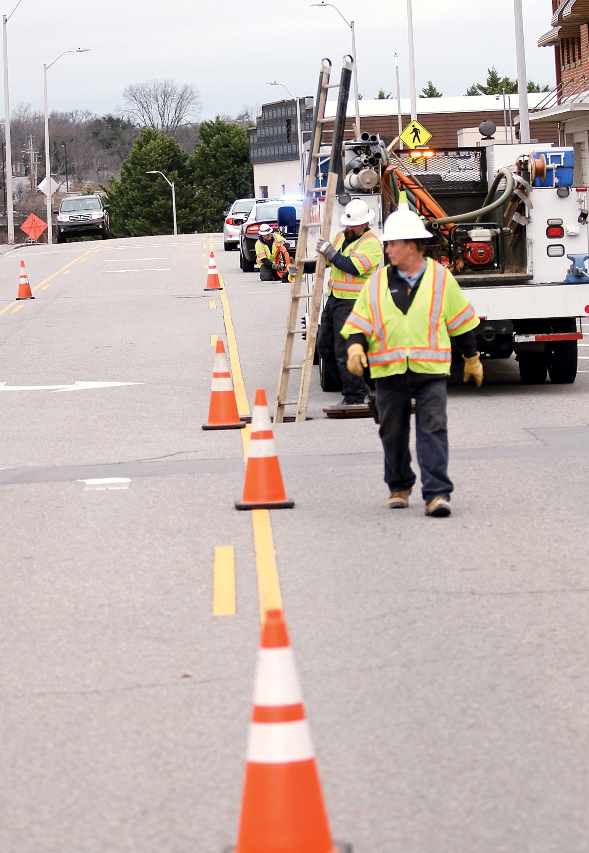 Workers install fiber optic cable along Harper Avenue