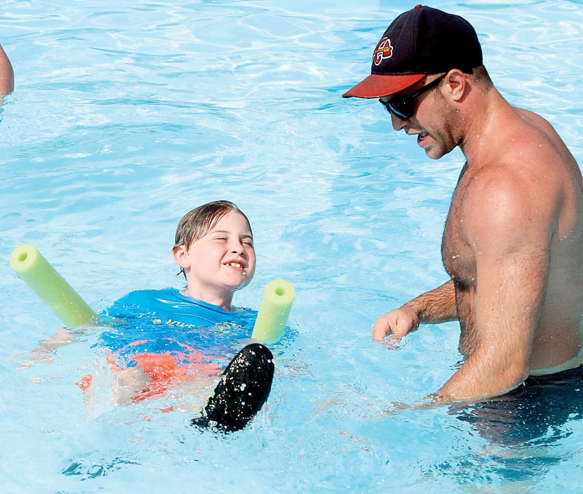 John Sevier Elementary teacher Alex Rouse helps James Anderson at the pool