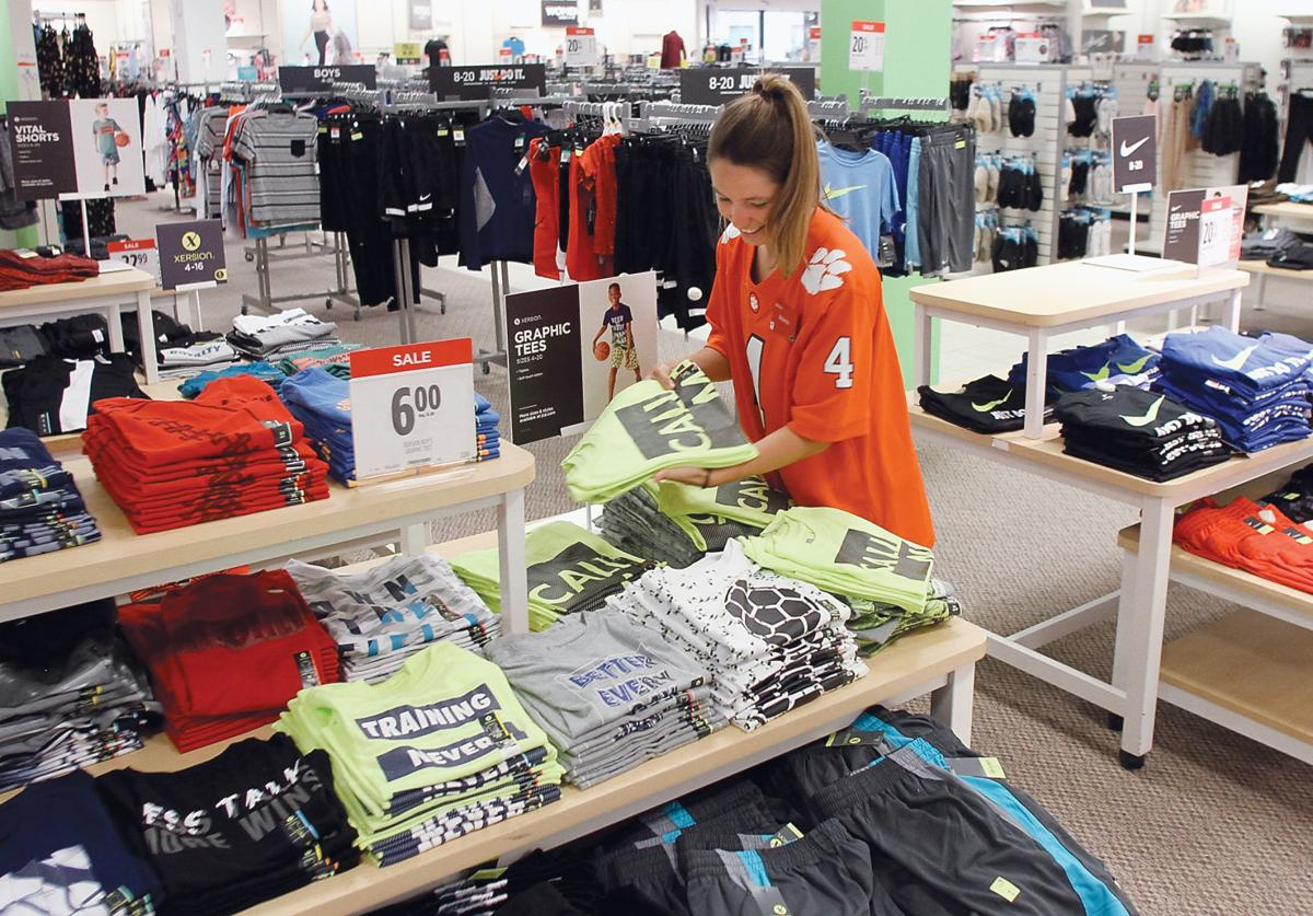 Brianna Williamson straightens clothing in the children's department at JC Penney