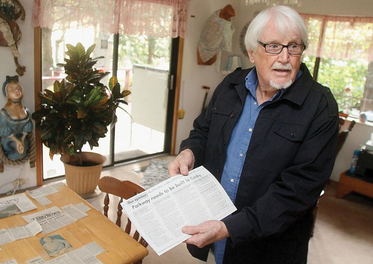 Rob Roberson shows some of his collection of newspaper articles about the Foothills Parkway