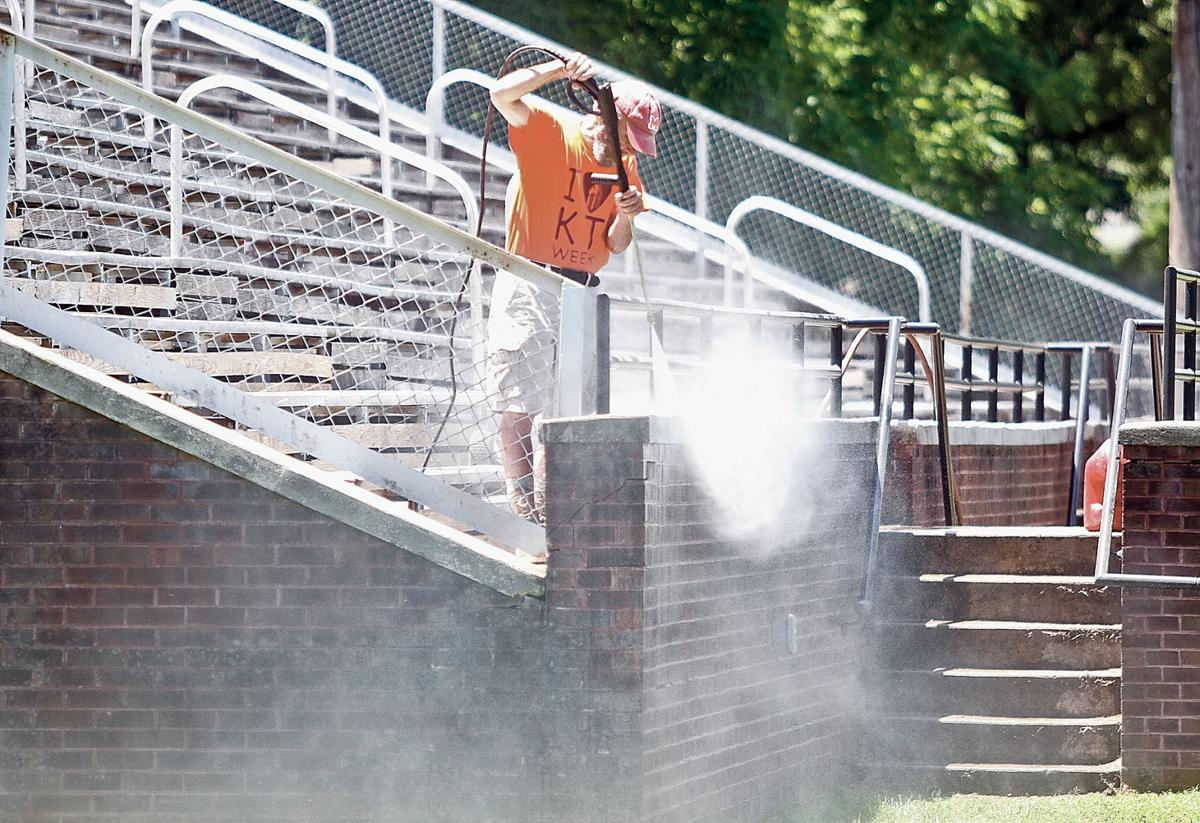 Davis Morris, Maryville College Class of '71, pressure washes the football bleachers during Kin Takahashi Week