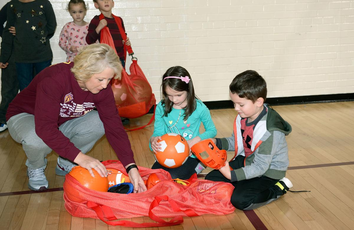 Rockford Elementary School's Leesa Taylor shows PE at Home equipment to Lily and Graham Stines