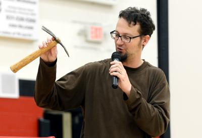 Shane Claiborne shows Maryville High School students a hand plow made from a gun