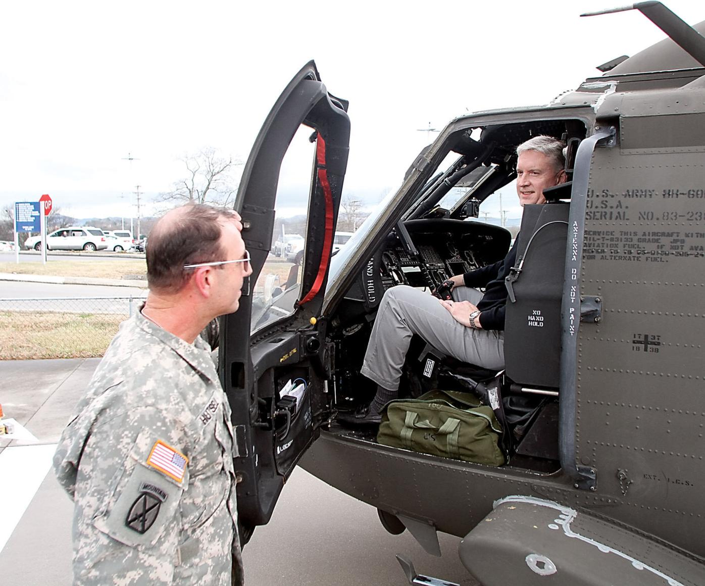 Don Heinemann talks with Chief Warrant Officer 4 Brad Hutsell as he sits in the cockpit of the Black Hawk