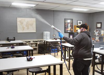 Head custodian Bubba McKenzie uses Clorox Total 360 System to sanitize an Eagleton Middle School