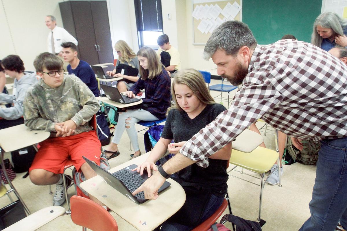 Teacher helps freshman with Chromebook