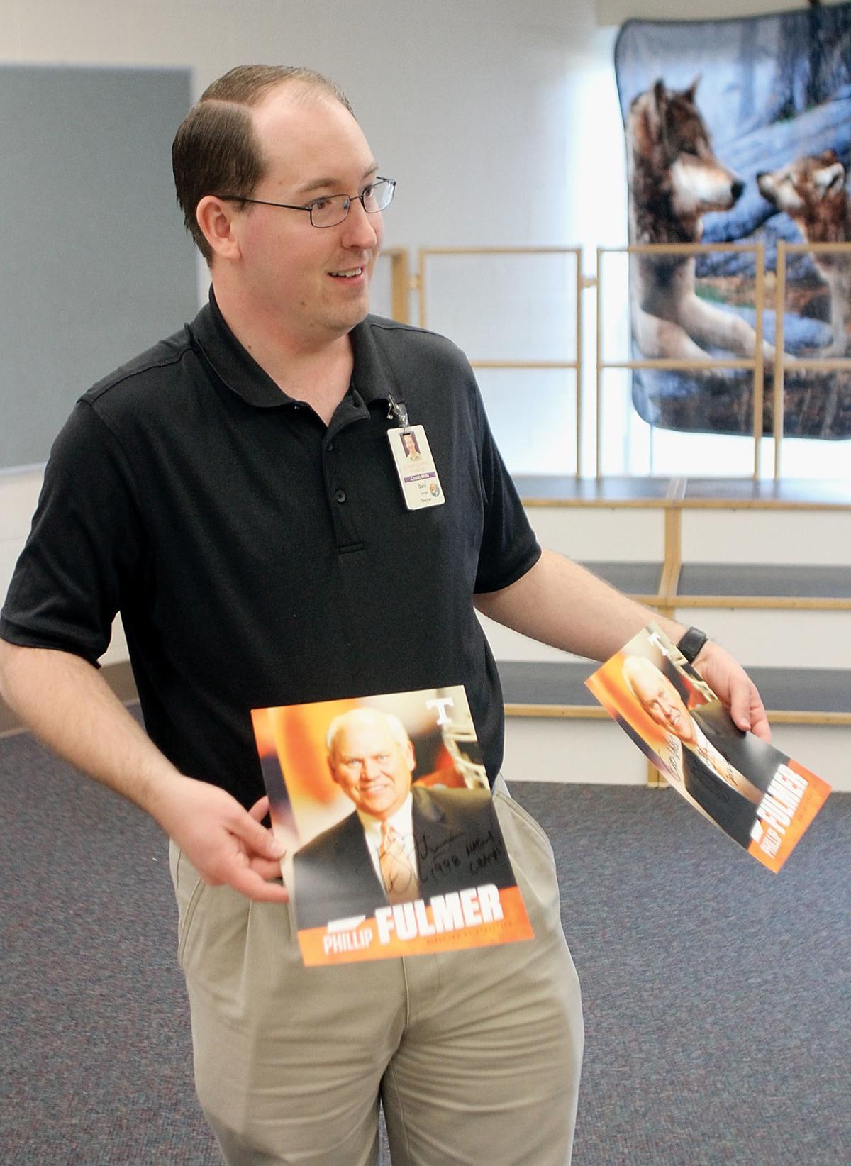 Music teacher James Gann shows two autographed photos of Phillip Fulmer