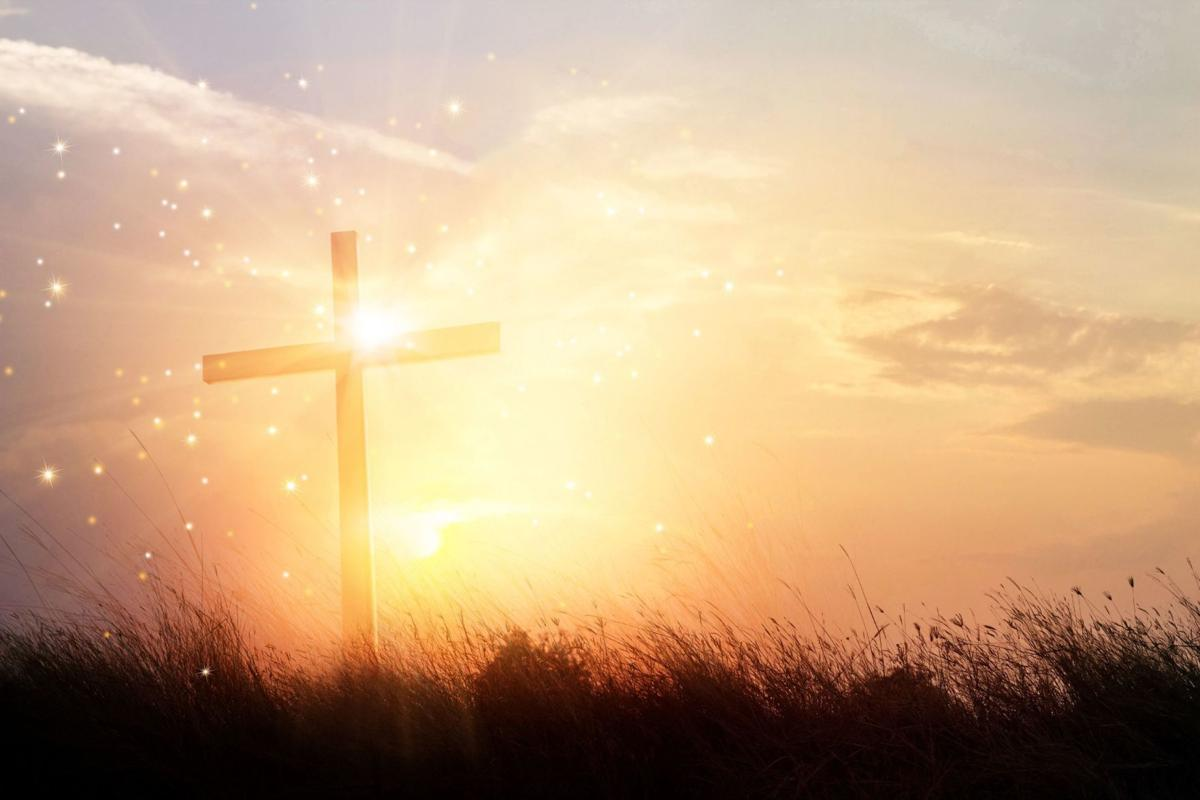 Silhouette christian cross on grass at sunrise background