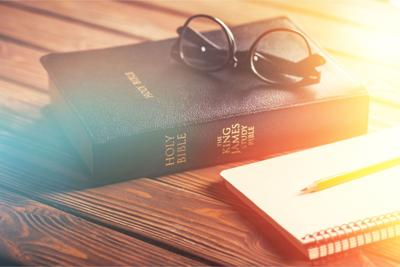 Holy bible with note book on desk