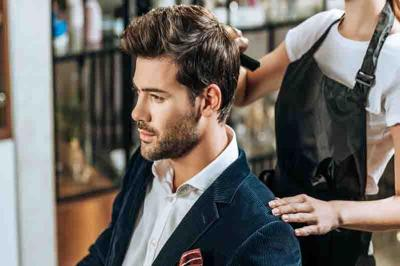 cropped shot of hairstylist combing hair to handsome young man in beauty salon