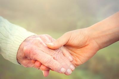 38790500 - elderly woman holding hands with young caretaker