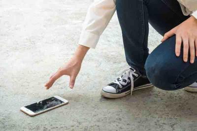 Person Picking Broken Smart Phone of Ground