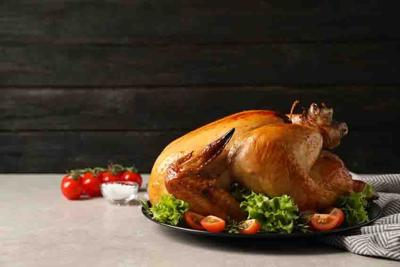 Platter of cooked turkey with garnish on table. Space for text