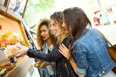 Three beautiful young women visiting eat market in the street.
