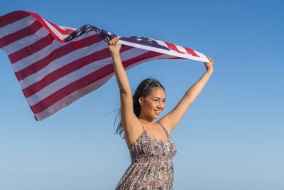 pretty and happy girl holds a flag of the United States against the sky. July 4th Independence Day.