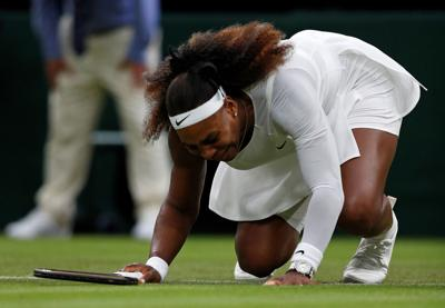 A leg injury brings Serena Williams to her knees before withdrawing from her women's singles first-round match against Belarus's Aliaksandra Sasnovich on the second day of the Wimbledon Championships at The All England Tennis Club in London, on Tuesday, June 29, 2021.