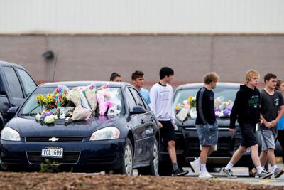 Memorials are seen at three vehicles parked at Gretna High School.