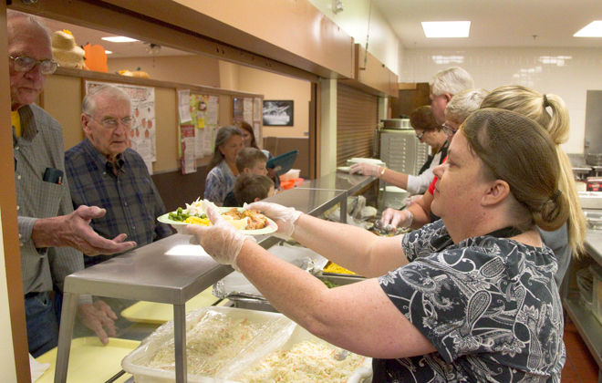 wanda winder serves a plate of food sunday at the grand generation center during project hunger s harvest festival fundraiser chicken and pheasant were the