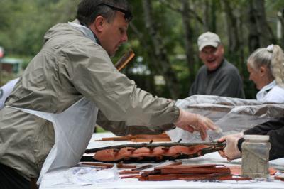 Removing freshly baked salmon from alder stakes(2).jpg