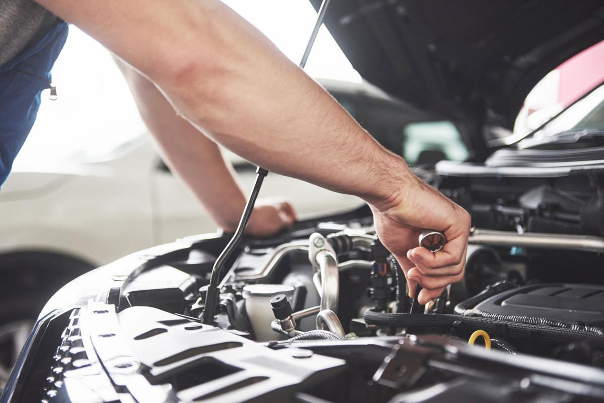 Auto mechanic working in garage. Repair service