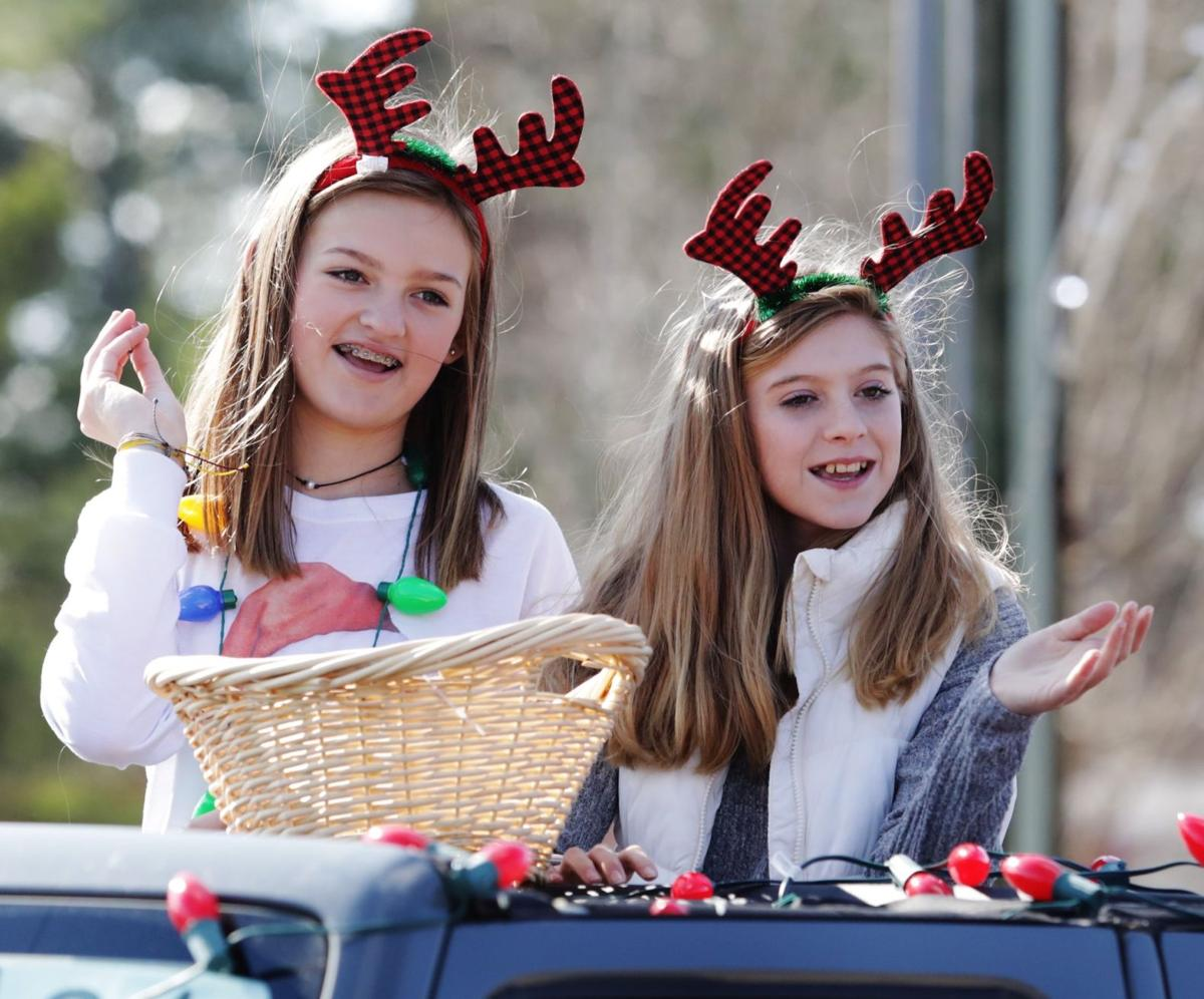 All decked out in antlers, Lyndee Meadows and Ella Waites toss candy to parade-goers.