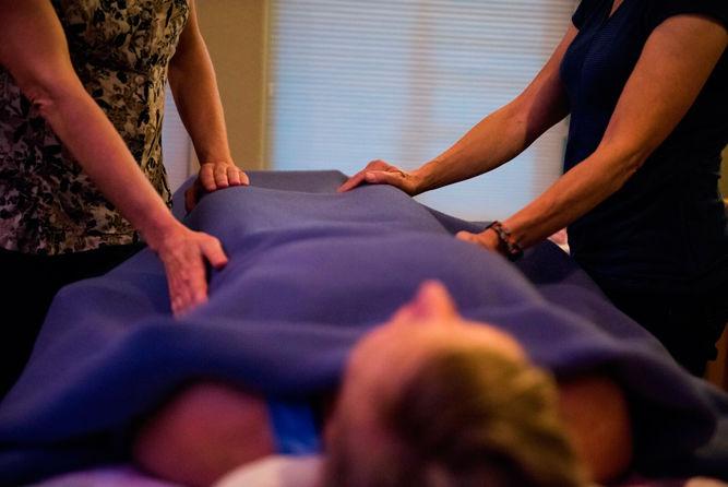 Reiki practitioner BJ Babcock of Ridgefield demonstrates the healing arts modality for Debbie Heurion of Ridgefield.