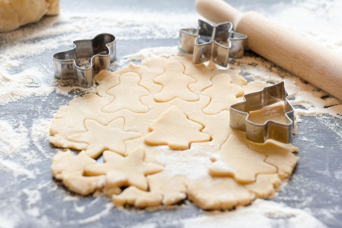Making homemade Christmas cookies.The dough and shape on a dark background