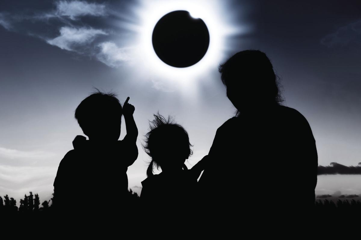 Silhouette back view of family looking at solar eclipse on dark sky background.