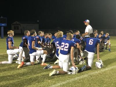 Nashville football coach Stephen Kozuszek in team huddle