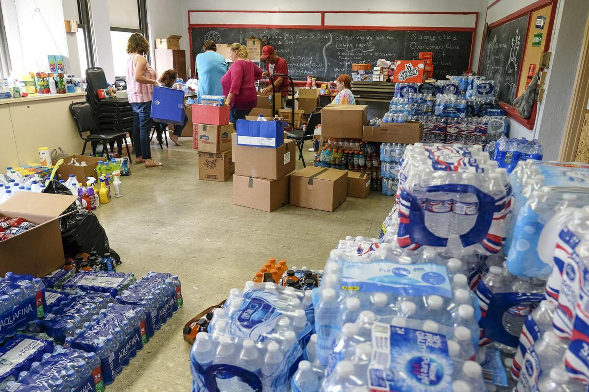 Volunteers box up food and supplies