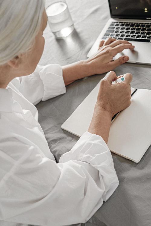 _an-elderly-woman-taking-notes-while-using-a-laptop-4057764_CMYK.jpg