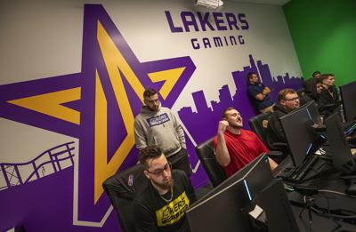 """Foreground, left to right: """"Mooty"""" Mitchell Franklin, 25, """"Detoxys"""" Christopher Doyle, 23, """"Vert"""" Jordan Gates, 20, """"Kev"""" Kevin Alvarado, 19, and """"KentruL"""" Christopher Cantrell, 22, members of the Los Angeles Lakers NBA 2K league, scrimmage against the Miami Heat 2K team, while inside the gaming room at the Lakers practice facility in El Segundo, Calif. In the background, left, is team member """"SafiyauYa"""" Shane Farrar, 27."""