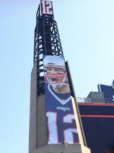 2ad6d6fed31e6 Banners featuring photos of Patriots  quarterback Tom Brady and placards  sporting his uniform number adorn the faux lighthouse in the north end zone  at ...