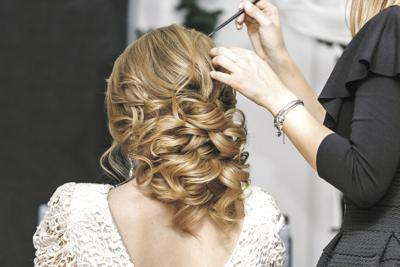 Young bride getting her hair done before wedding by professional