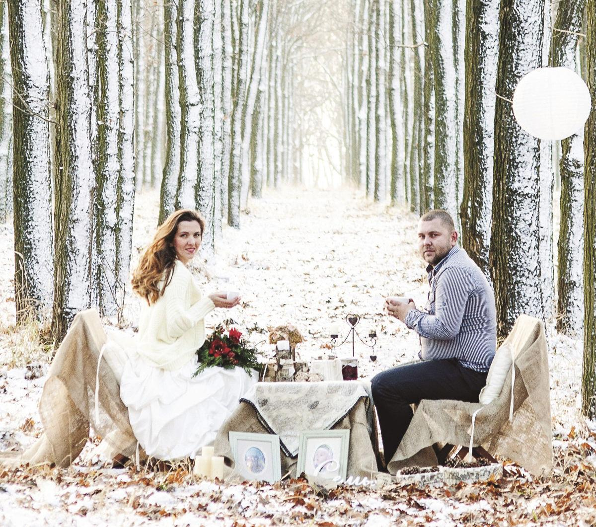 Winter wedding newlyweds sitting at a decorated table in rustic