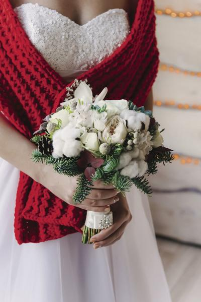 Bride in a white dress and red scarf with a white bouquet in her hands, winter wedding