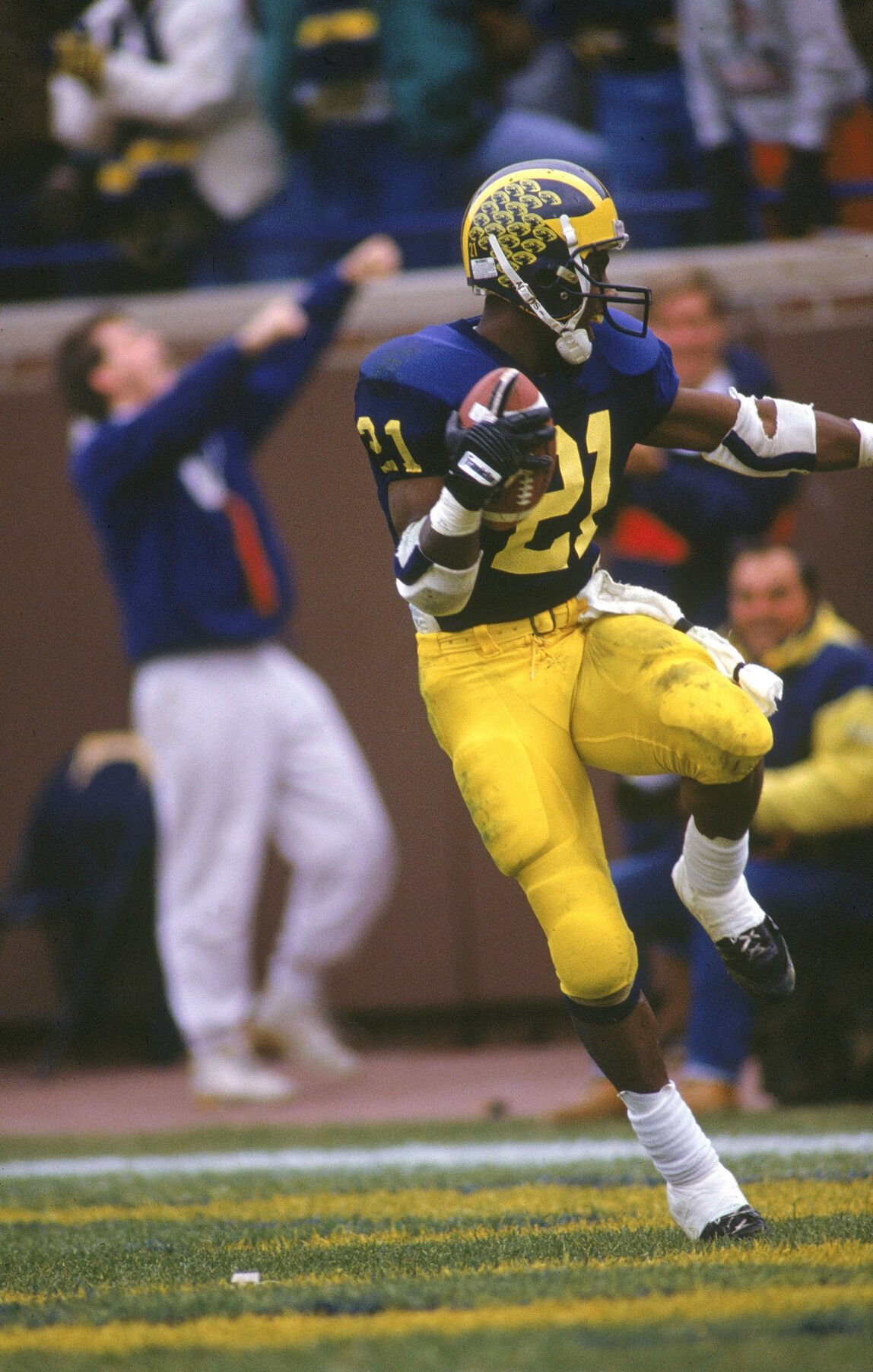 In this file photo, Desmond Howard of the Michigan Wolverines runs in the the' Heisman' pose right after making a 93 yard touchdown against Ohio State circa 1991 in Ann Arbor, Michigan.