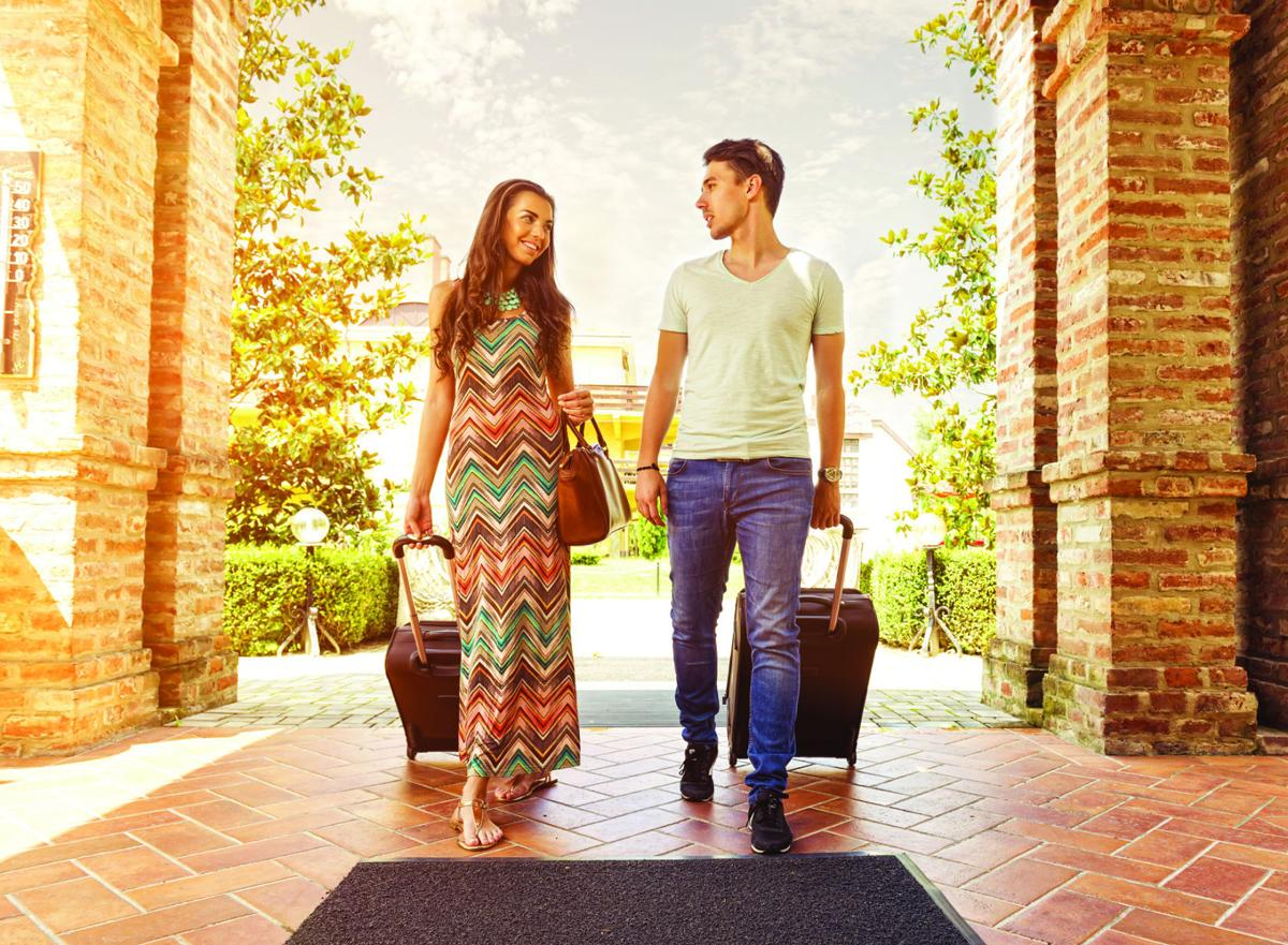 Young couple standing at hotel corridor upon arrival