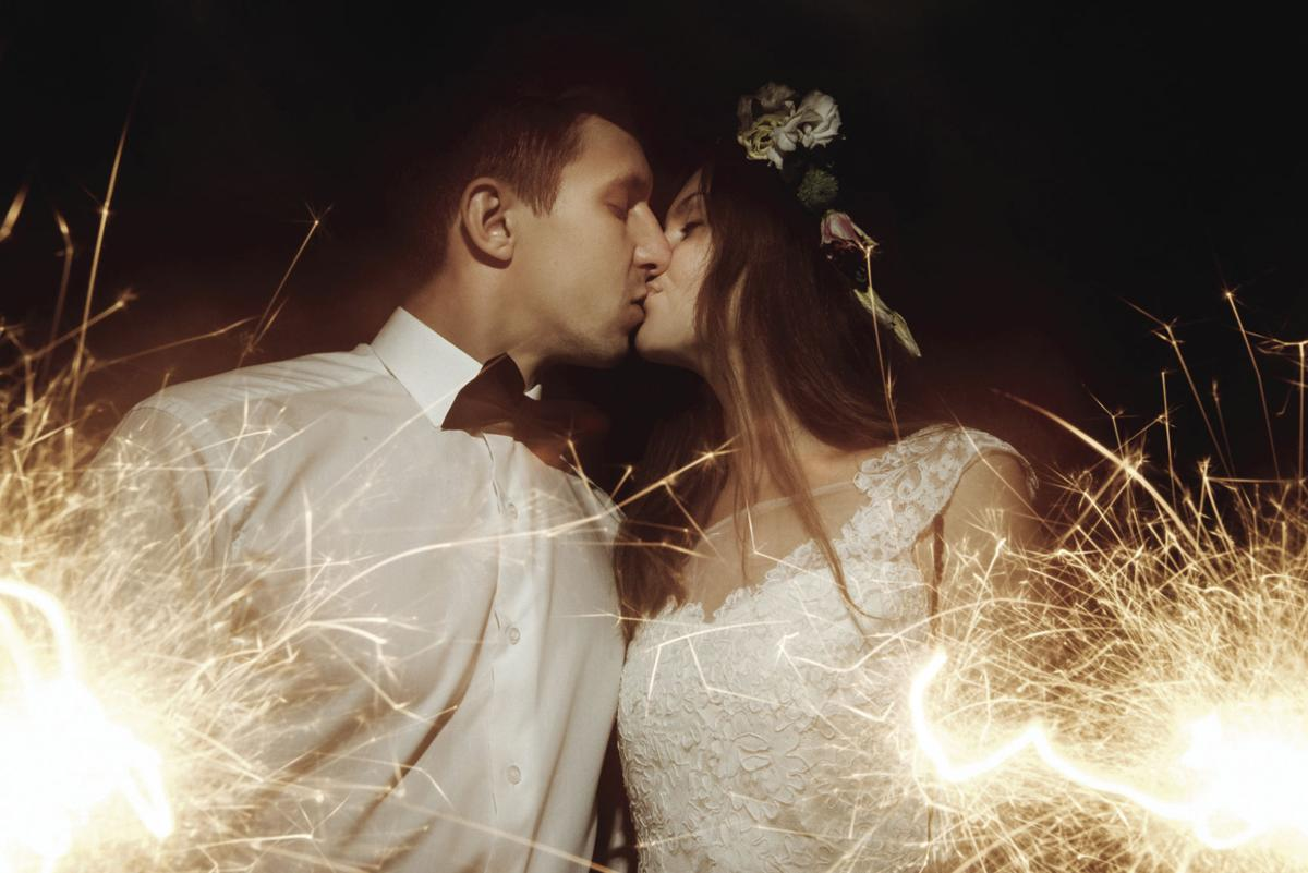 happy beautiful bride and elegant stylish groom holding fireworks on the top of a mountains in the evening