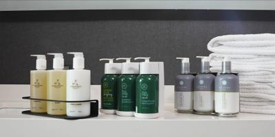 Marriott International pledges to replace tiny toiletry bottles with larger, pump-topped bottles that are fastened to the bathroom walls.
