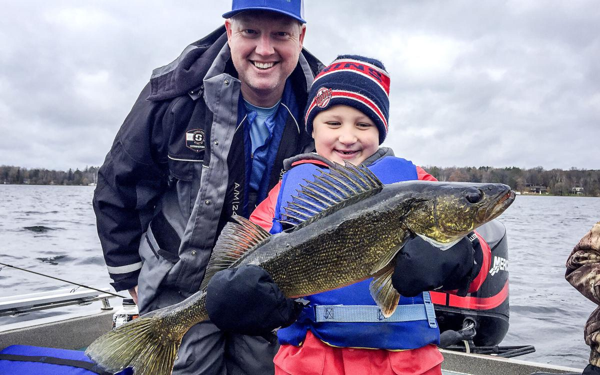 Catch Your Moment Foundation founder Timmon Lund of Duluth, left, and cancer survivor Liam Schmid of Nowthen, Minnesota, pose with a big walleye Liam caught on a 2018 Catch Your Moment trip. Liam has been cancer-free for nearly two years.