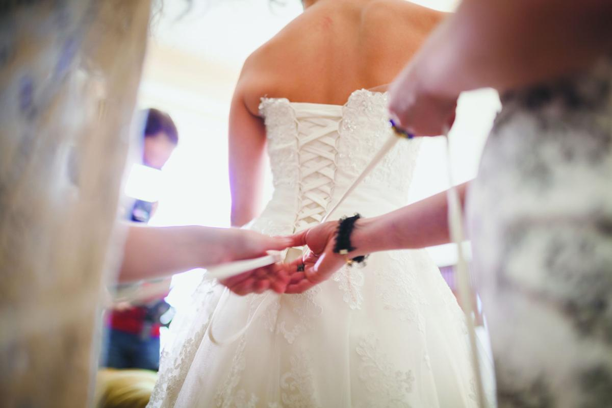 bride's friends help to fit the wedding dress