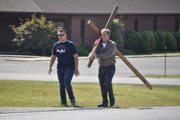 Two men carry cross through town to raise money for needy children