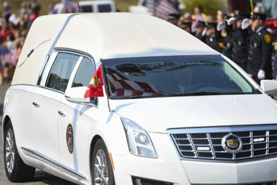 The hearse carrying the remains of U.S. Marine Corps Cpl. Humberto Sanchez, of Logansport, stops for 30 seconds under the garrison flag, which is reflected in the windshield, during the Marine's homecoming procession in Logansport on Sunday.