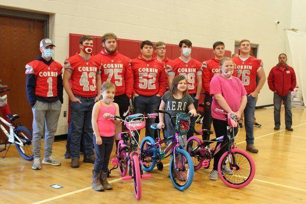 CHS football seniors helpgive away bikes to local children