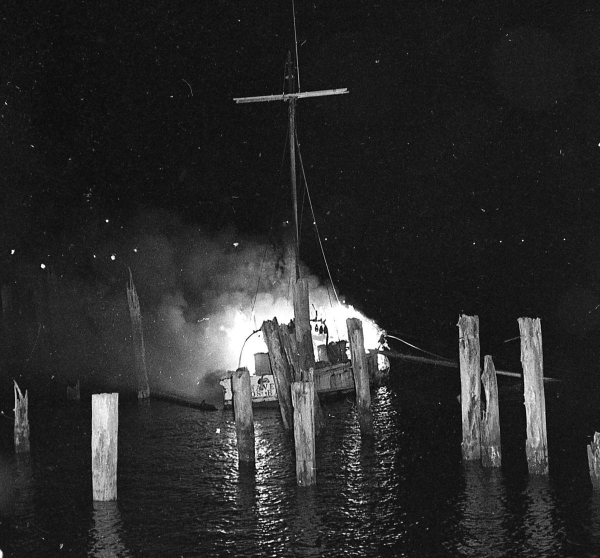 FV Waves, owned by Mike Erdman, burns near pilings behind MM truck shop, Aug. 1977,
