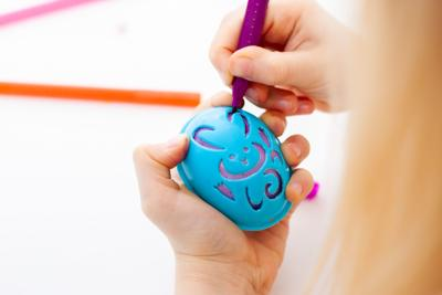 Little girl is preparing for Easter and painting eggs. Colorful markers. Rabbit template pattern.