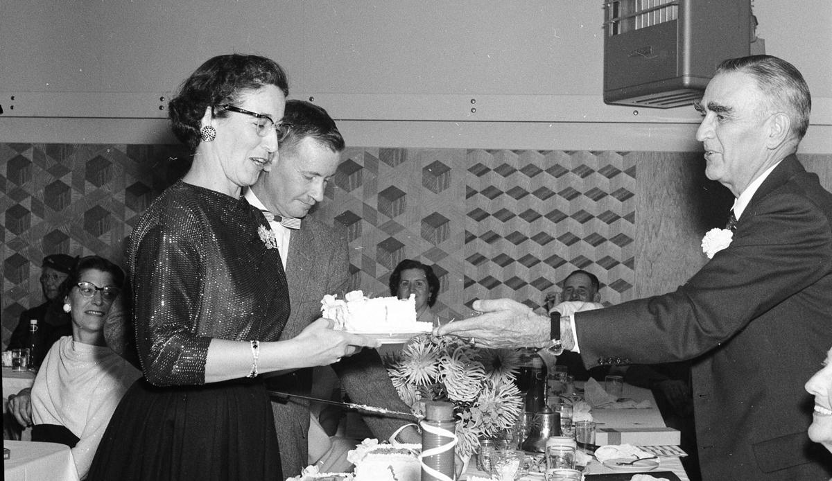 Dr. E.F. Lucas given a piece of cake by Margaret Norton as Eddie Waldrop cuts the cake; behind is Grace Dobney; at end of table, Irene and Howard Kehl, Sept. 1957